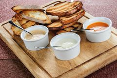La fetta di pane tostato ha arrostito dentro impanato con formaggio e slittato con salsa su un bordo di legno Immagine Stock Libera da Diritti