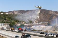LA Feuerwehrhubschrauber, der feuerverzögernde nahe Autobahn fallenläßt lizenzfreies stockbild