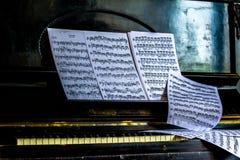 La feuille avec des notes s'étend sur le piano rétro Images stock