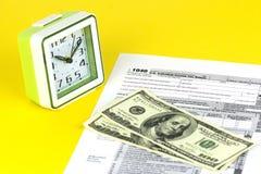 La feuille d'impôt américaine 1040 est sur la table Quelques factures sont sur le dessus Argent liquide de 100 dollars et réveils image libre de droits