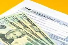La feuille d'impôt américaine 1040 est sur la table Quelques factures sont sur le dessus Argent liquide de 20 et 100 dollars photos libres de droits