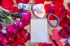 La feuille de papier, de stylo et de pétale rouge s'est levée Photo libre de droits