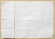 La feuille de papier texturisée blanche s'est pliée dans seize parts Images libres de droits