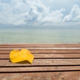 La feuille jaune sous la forme de coeur sur la mer de table en bois et de ciel nuageux d'automne échouent le fond Image stock