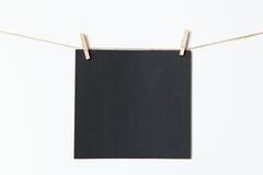 La feuille noire pour appliquer le texte est jointe par les pinces à linge en bois Photographie stock
