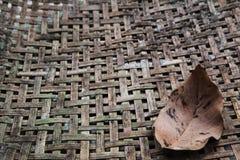 La feuille sèche sur la texture du bambou a tissé le fond Images stock