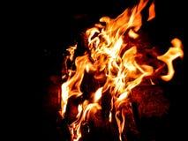 La fiamma arancio con le scintille, un fuoco di accampamento è stata lasciata dopo avere grigliato gli spiedi brucia nello scuro fotografia stock