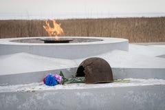 La fiamma eterna, in memoria delle vittime di 1941-1945, una pallottola ha perforato il casco Fotografia Stock