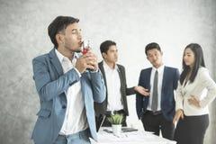 La fierté heureuse d'homme d'affaires avec la tasse de victoire et les affaires team jaloux photos libres de droits