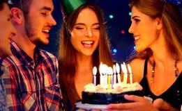 La fiesta de cumpleaños feliz de los amigos con la celebración de la vela se apelmaza Imagenes de archivo