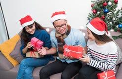 La fiesta de Navidad con los amigos, gente de Asia intercambia el regalo y el givi Foto de archivo