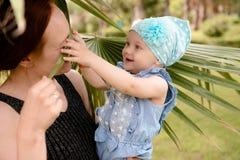 La figlia è giocata con una foglia di palma ed il suo naso del ` s della madre Immagine Stock Libera da Diritti