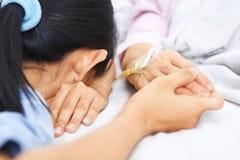 La figlia cade addormentato attendendo la sua madre ammalata Immagini Stock Libere da Diritti