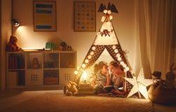 La figlia del bambino e della madre con un libro e una torcia elettrica prima va Fotografia Stock