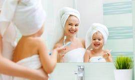La figlia del bambino e della madre pulisce i loro denti con lo spazzolino da denti fotografia stock libera da diritti