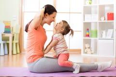 La figlia del bambino e della madre si è impegnata nella forma fisica, yoga, si esercita a casa Immagine Stock
