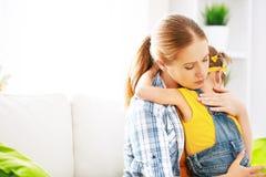 La figlia della ragazza del bambino dentro abbraccia sua madre Fotografia Stock