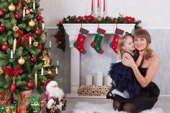 La figlia felice abbraccia l'ubicazione della madre vicino ad un camino bianco accanto ad un albero di Natale Fotografia Stock