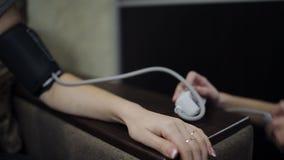 La figlia misura la pressione facendo uso di un apparecchio elettronico sua madre video d archivio