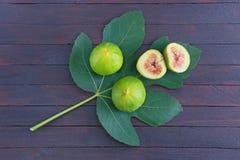 La figue mûre porte des fruits avec la feuille verte du figuier sur le fond foncé Configuration plate images stock