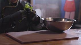 La figura borrosa de los rasgones del cocinero se va del perejil y pone en el cierre de aluminio grande del cuenco Preparación de almacen de metraje de vídeo