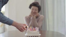 La figura borrosa de la señora sonriente positiva que se sienta en la tabla en el fondo mientras que las luces de la mano del hom almacen de video