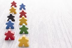 La figura de madera blanca en la forma de un hombre se coloca sobre otros detalles Partes del juego de mesa foto de archivo