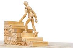La figura de madera sube una escalera de madera como símbolo del adelanto de la carrera imagen de archivo libre de regalías