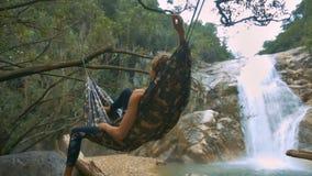 La figura de la muchacha miente en hamaca suave en la vista lateral trasera de la cascada