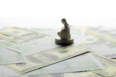 La figura de un hombre del juguete que se sienta en su rodilla en el dinero Foto de archivo