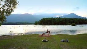 La figura della ragazza cambia le pose di yoga contro il lago piacevole stock footage