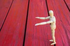 La figura di legno che solleva il braccio/mano e presenta Fotografie Stock
