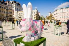 La figura di un coniglietto di pasqua bianco con le uova di Pasqua dipinte su nel colore rosa e porpora Bella arte della decorazi Immagine Stock Libera da Diritti