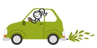 La figura feliz mujer del palillo que sonríe y que conduce el coche amistoso del pequeño eco verde con verde se va en vez de humo Fotos de archivo