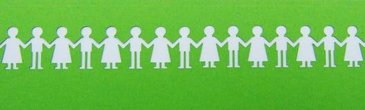 La figurina dei bambini della carta si tiene per mano su fondo verde immagine stock