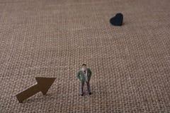 La figurine et la flèche ont coupé du papier brun près d'un coeur Image stock