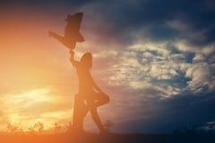 La fijación de la forma de vida de la mujer de la silueta se relaja en la puesta del sol Imágenes de archivo libres de regalías
