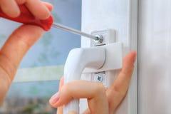 La fijación de la manija de ventana atornilla con destornillador manual, da el cl Imagen de archivo