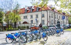 La fila de la ciudad bikes para el alquiler en las estaciones de acoplamiento en la ciudad vieja, Varsovia Foto de archivo libre de regalías