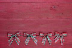 La fila de la Navidad roja de la tela escocesa arquea el fondo de madera rojo antiguo de la frontera imagenes de archivo