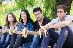 La fila de los amigos que se sientan junta come el plátano foto de archivo libre de regalías