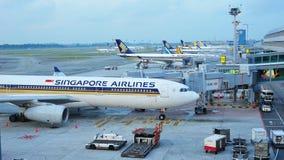 La fila de los aviones de Singapore Airlines, de Tiger Air y de Silkair parqueó en el aeropuerto de Changi imagen de archivo libre de regalías