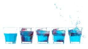 La fila de los cócteles frescos azules del alcohol en un vidrio se mezcló con al rojo imagenes de archivo
