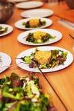 La fila dei piatti con insalata è servito sulla tavola Fotografia Stock