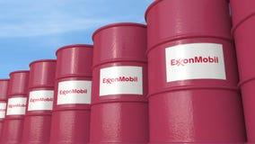 La fila del metal barrels el logotipo de ExxonMobil Corporation contra el cielo, representación editorial 3D Stock de ilustración
