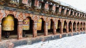 La fila del rezo budista amarillo tradicional rueda adentro la pared, Bhután Imagen de archivo libre de regalías