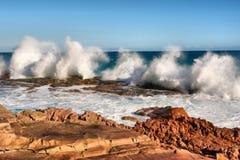 La fila dell'onda spruzza sulla spiaggia rossa della roccia fotografia stock