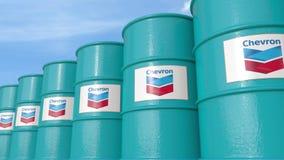 La fila di metallo barrels con il logo di Chevron Corporation contro il cielo, rappresentazione editoriale 3D Fotografie Stock Libere da Diritti