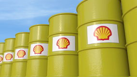 La fila di metallo barrels con il logo di Royal Dutch Shell contro il cielo, rappresentazione editoriale 3D Immagini Stock Libere da Diritti