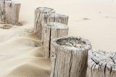 La fila irregular de los polos de madera viejos de la playa significó funcionar como el rompeolas fotografía de archivo libre de regalías